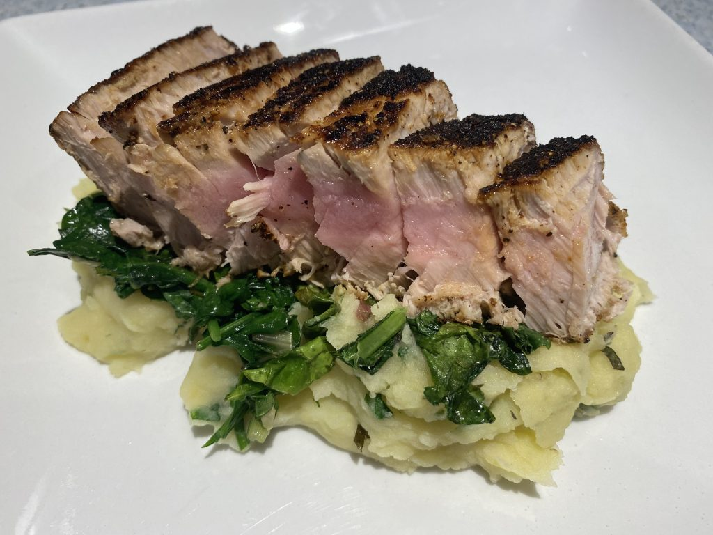 Seared, blackened ahi tuna steak sits atop garden fresh greens sautéed with garlic and healthy mash made with chicken broth
